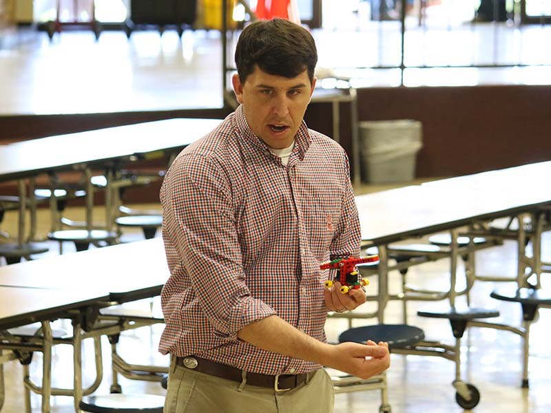 a teacher at the gym holding a lego